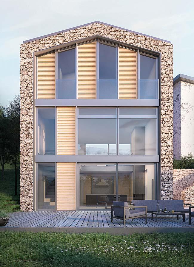 Pedras brutas formam uma moldura ao redor dessa casa sobrado