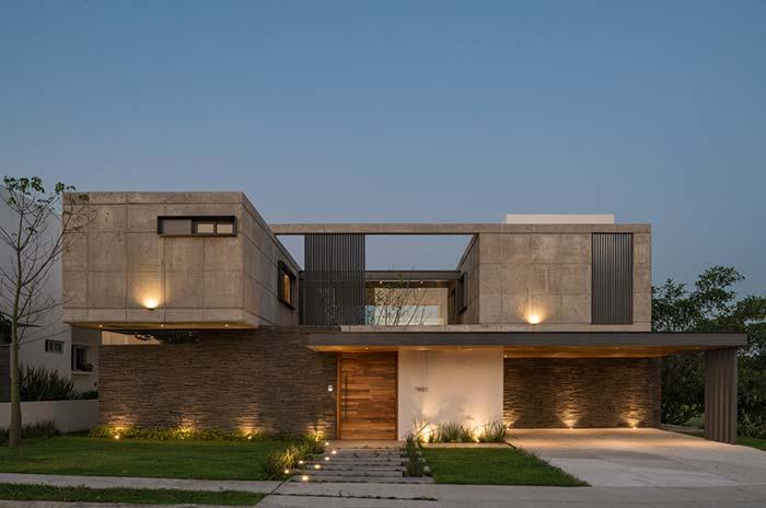 Sobrado com fachada de concreto aparente e pedras
