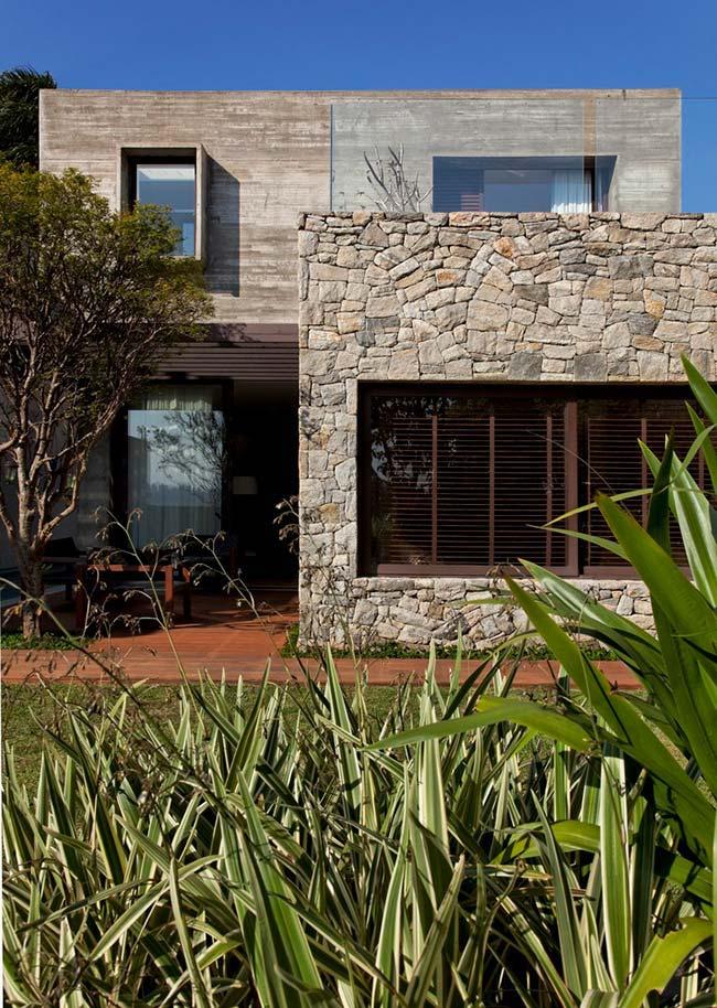 Essa fachada de casa com pedra foi feita com uma combinação entre pedras e concreto aparente
