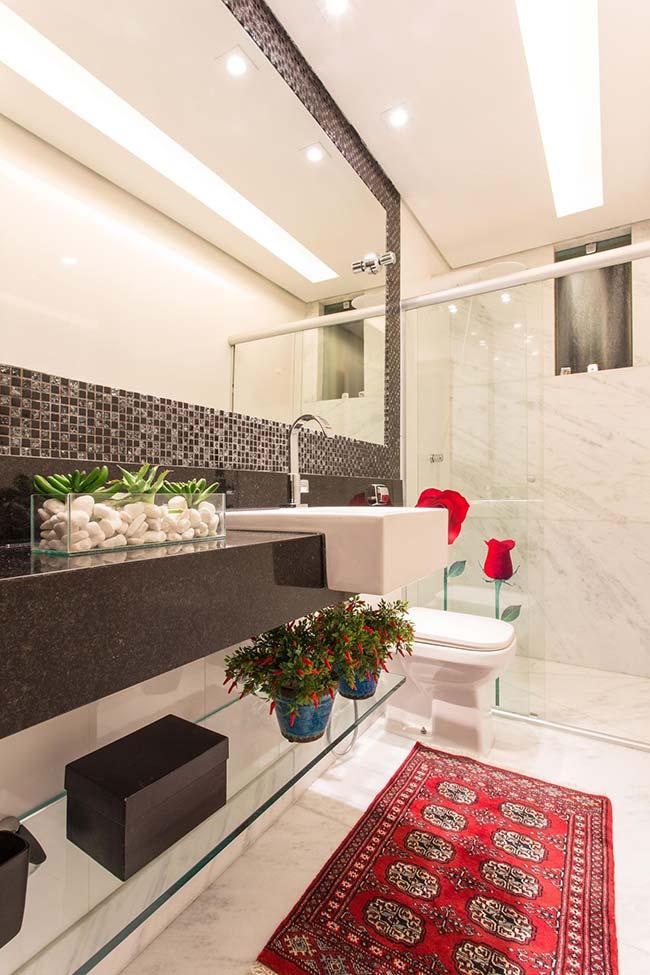 Preto e cinza escuro das pastilhas de vidro é realçado pelos pontos em vermelho presente nesse banheiro