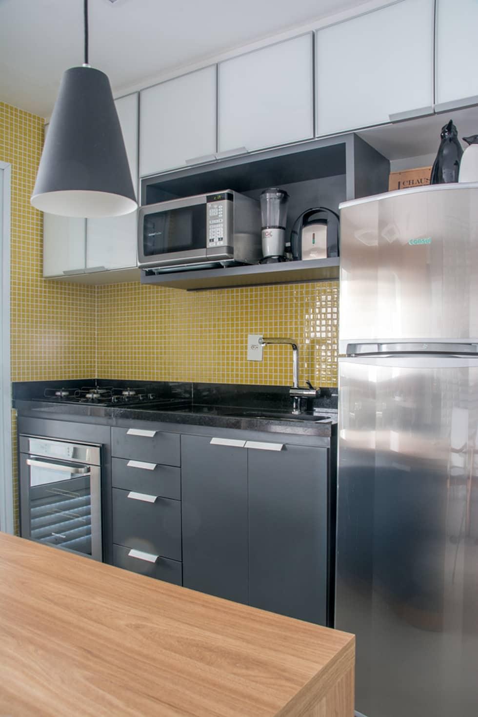 As pastilhas de vidro amarelas dão um toque de cor para a cozinha branca e preta