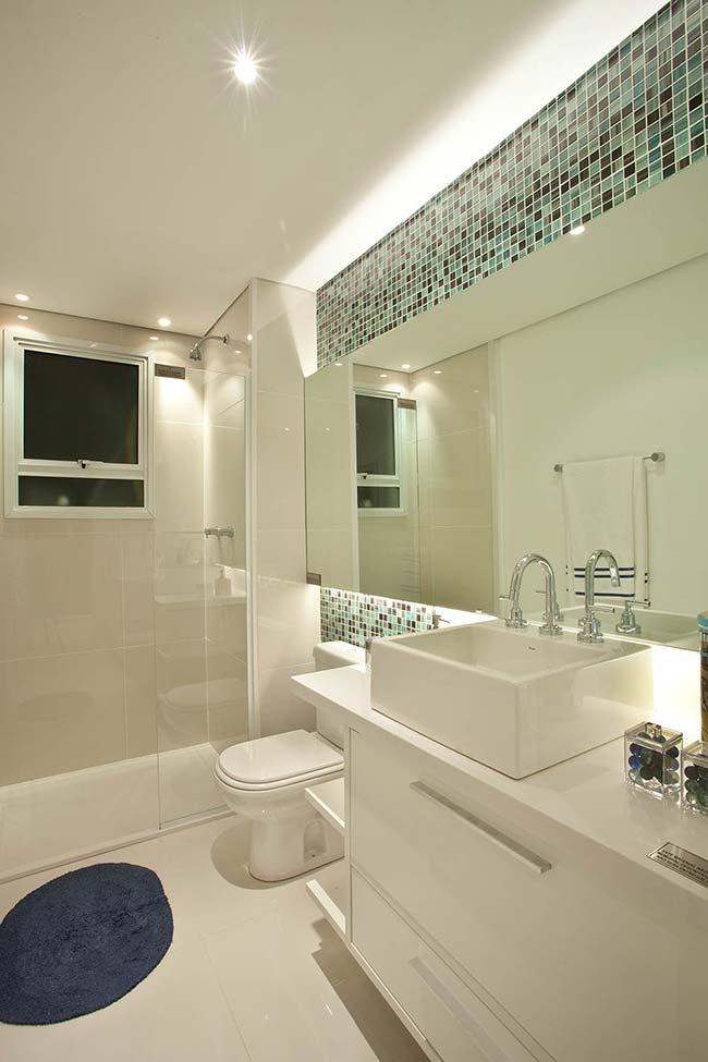 A parede principal desse banheiro foi valorizada com o uso das pastilhas de vidro
