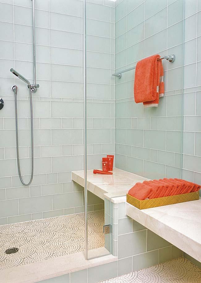Azul suave das pastilhas de vidro foi usado para revestir todas as paredes desse banheiro