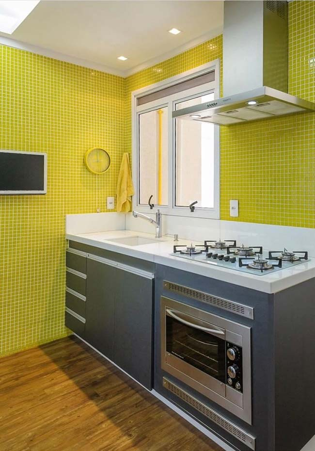 Pastilhas de vidro amarelas dão o tom para essa cozinha