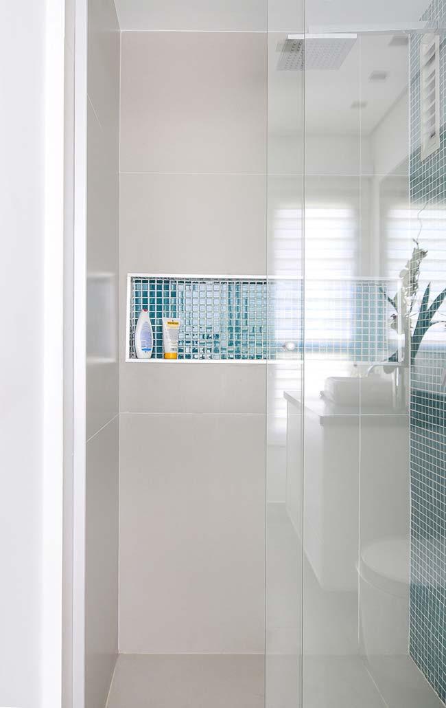 Pastilhas de vidro azuis são o detalhe sutil, mas suficiente para mudar a cara do banheiro branco