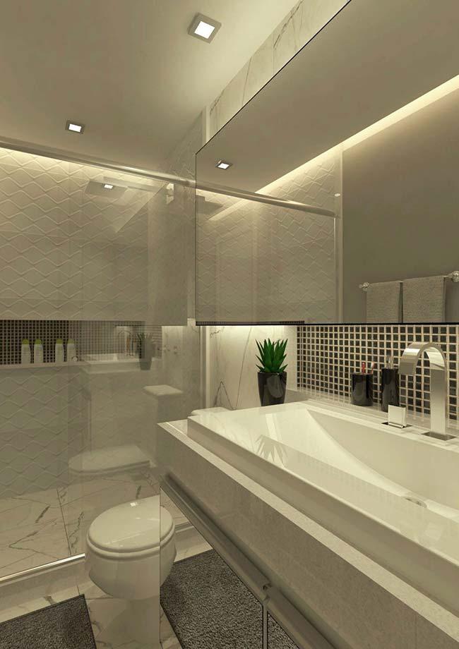 A faixa de pastilhas de vidro na cor preta reforça a proposta elegante e sofisticada desse banheiro