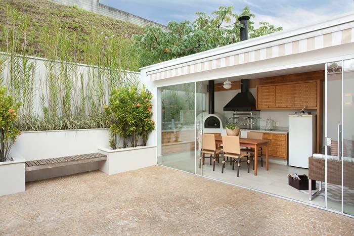 Edícula pequena com porta de correr de vidro; no interior, um espaço gourmet e uma sala de estar