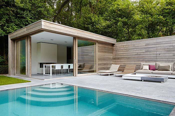 Edícula de madeira com portas de correr de vidro; a mistura de materiais ajuda a deixar a área mais elegante e sofisticada
