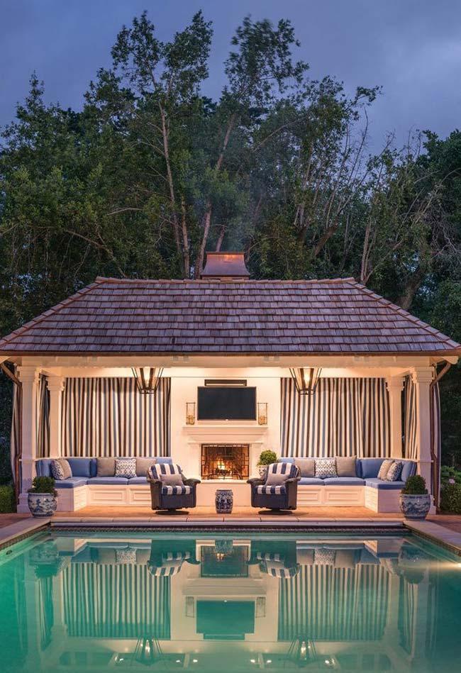 Edícula planejada para todas as estações: no verão, a piscina e no inverno, a lareira junto ao sofá
