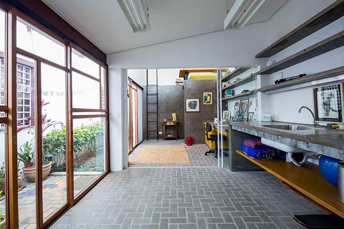 edícula de formato alongado abriga um banheiro, bancada de trabalho e cozinha externa