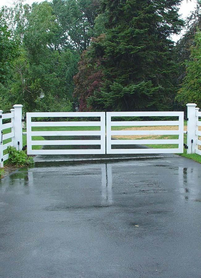 Portão branco acompanha o formato e a altura da cerca ao redor da chácar