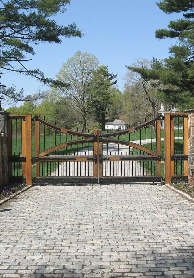 Para combinar com a alameda de paralelepípedos, um portão de madeira e ferro