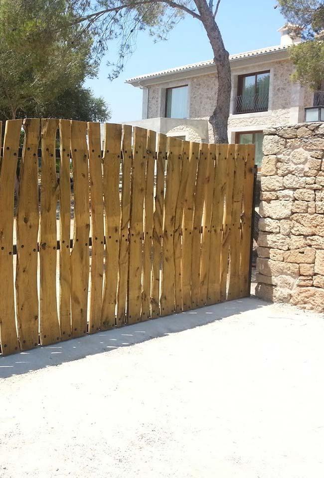 Entrada de chácara com portão de madeira; repare que as tábuas irregulares trazem um visual diferenciado para o local