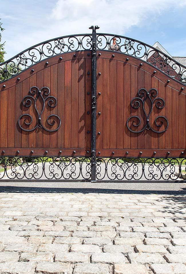 Portão de ferro com arabescos, para garantir a privacidade no interior da chácara, um tampo de madeira maciça