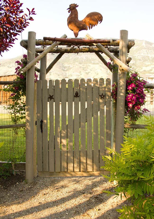 O portãozinho e o galo talhado em madeira sobre o pergolado fazem as honras para os visitantes que chegam a pé