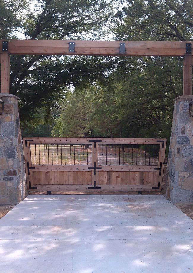 Madeira maciça, ferro e pedras conferem a essa entrada de chácara um estilo medieval