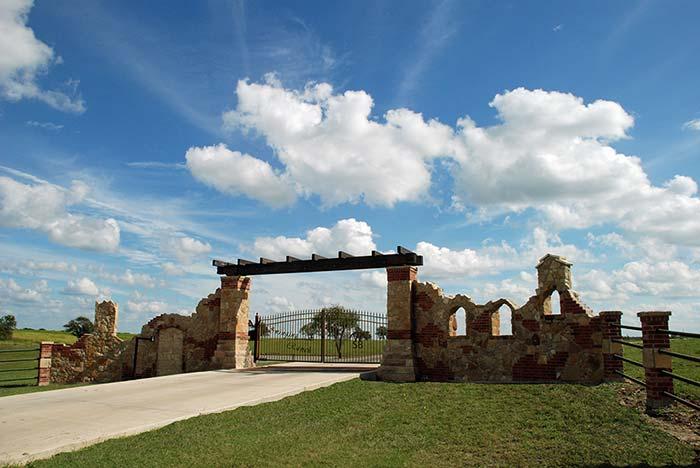 Uma entrada de chácara que mais parece uma fortaleza medieval feita com pedras e tijolinho