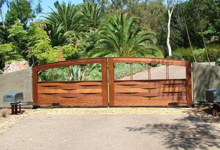 O muro de concreto fixa esse portão de madeira na entrada da chácara