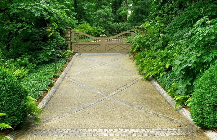 O chão com desenhos em pedra e o portão em curva são apenas um detalhe diante da exuberância do verde