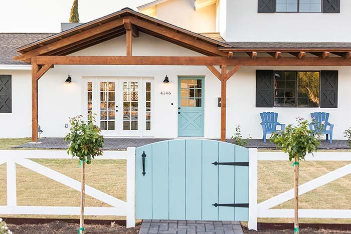 Cerca branca e portão azul claro formam uma entrada encantadora e muito charmosa