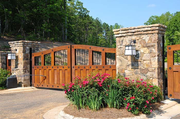 Canteiro de flores ajuda a compor a entrada dessa chácara, ao lado do portão de madeira e ferro e das colunas de pedra