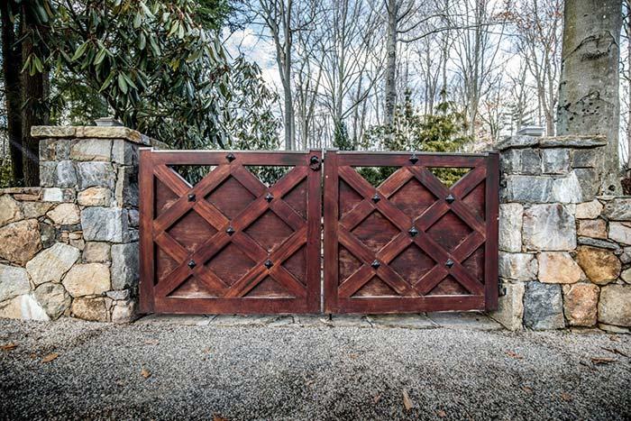 Entrada de chácara com portão desenhado de madeira e detalhes em ferro