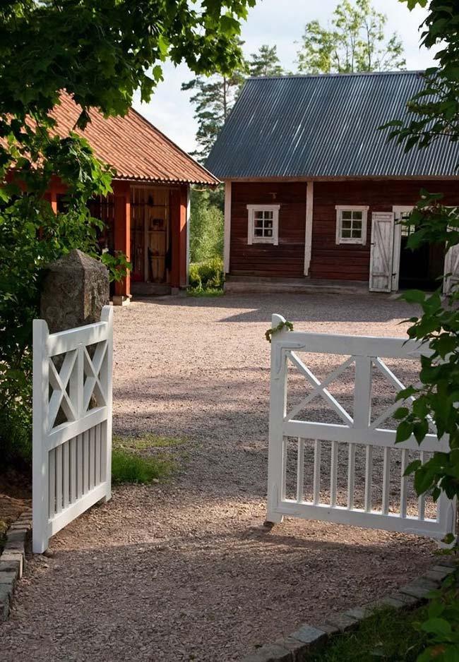 Portão simples de madeira pintada de branco foi fixado às colunas de pedra.