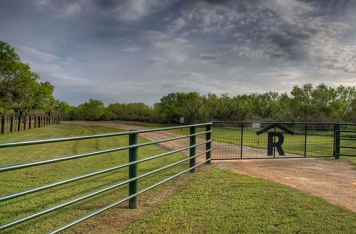 Portão de chácara com tela aramada seguindo a cor verde da cerca