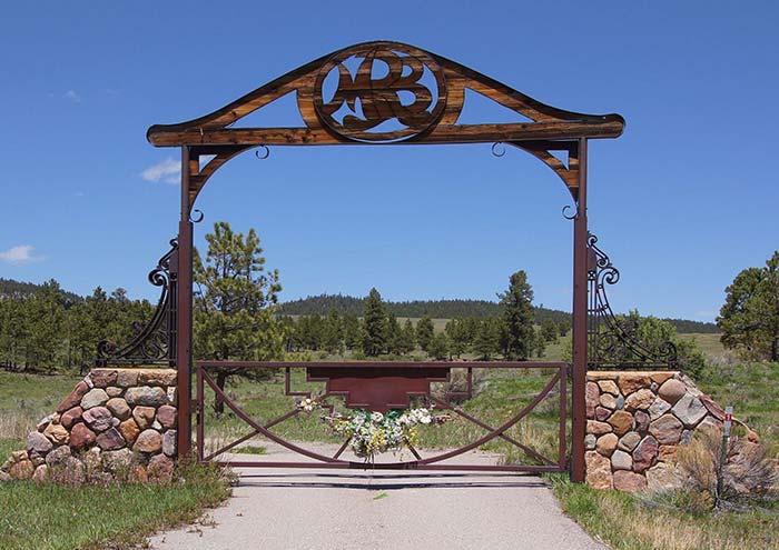 Guirlanda de flores ajuda a decorar o portão de ferro dessa entrad