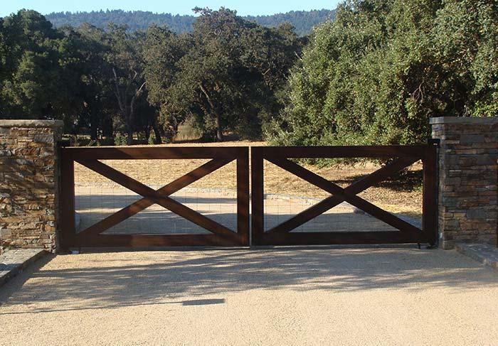 Tela de metal atrás do portão de madeira evita a entrada de animais na propriedade