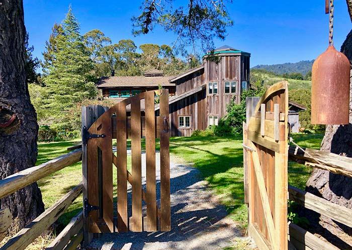 Nessa chácara, o portão pequeno de madeira recepciona quem chega de carro ou a pé