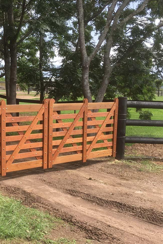 O portão simples de madeira dá sequência ao caminho de terra batida