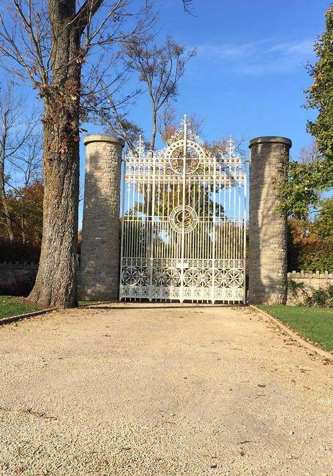 A entrada dessa chácara conta com um portão alto de ferro sustentado por duas frondosas colunas de pedra em formato circular