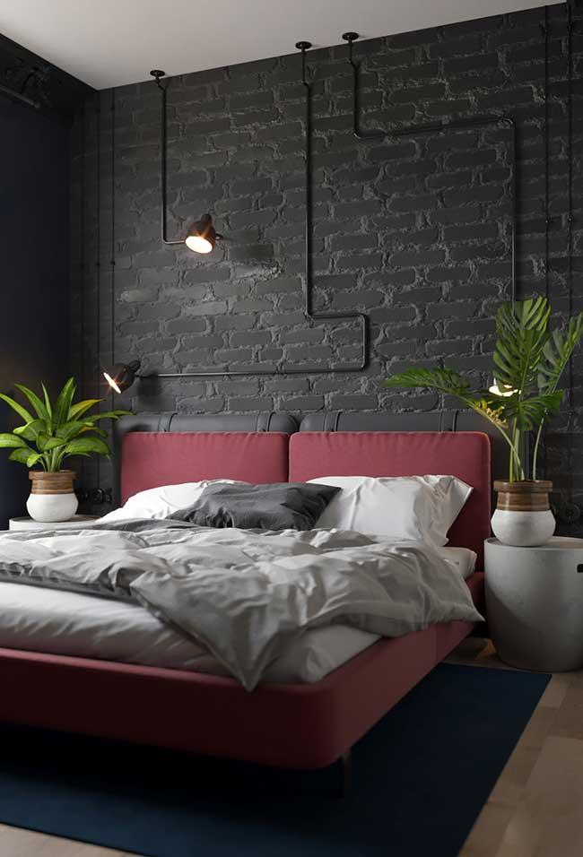 Nesse quarto de cores fortes e marcantes, o caminho feito pela tubulação termina com a luminária de parede