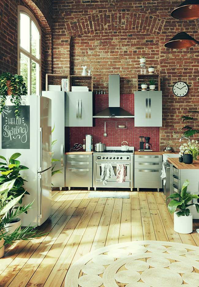 O pé-direito alto e os elementos em inox revelam a tendência industrial dessa cozinha, apesar do toque de rusticidade