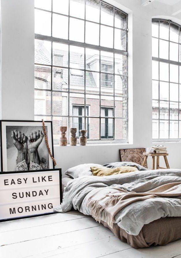 Cama no chão e janelas amplas: quarto de casal perfeitamente industrial
