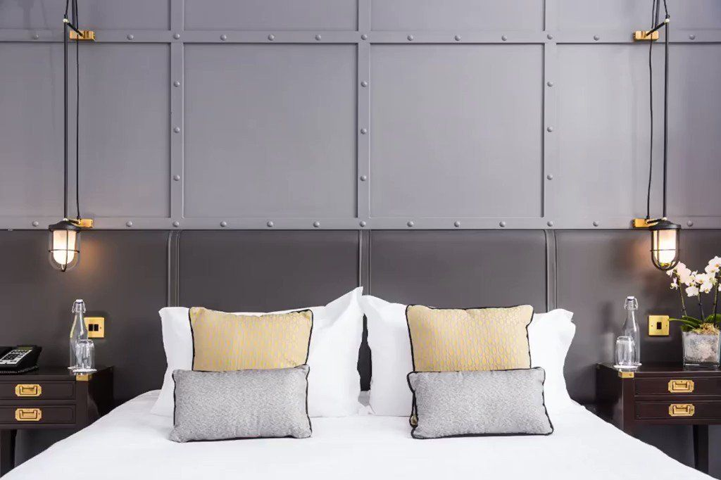"""Chapa de aço e cabeceira de couro: dois elementos de """"peso"""" para compor o estilo industrial desse quarto"""