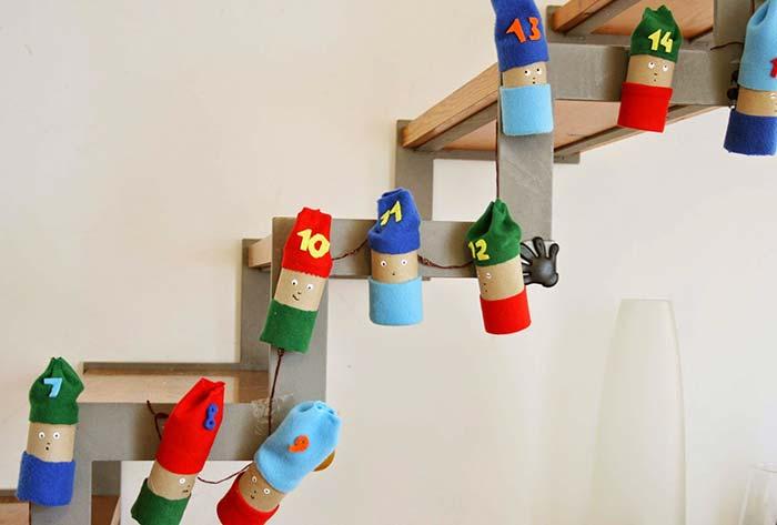 Decorando a lateral da escada com bonequinhos feitos com rolo de papel higiênico