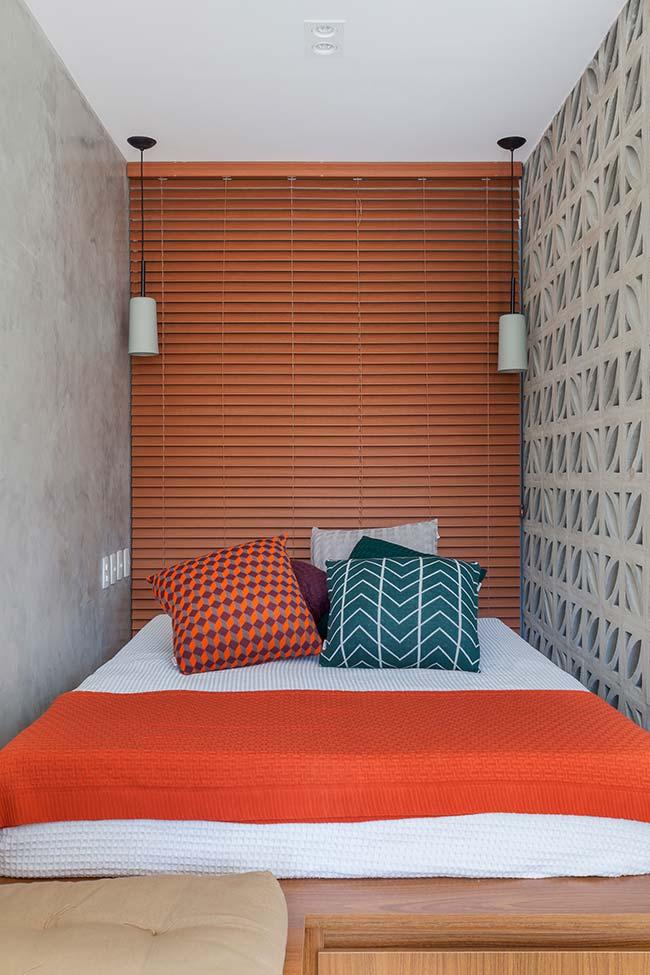 Quarto de casal pequeno e de paredes cinza apostou em uma persiana laranja