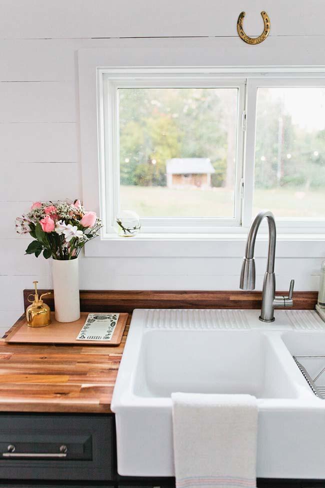 No cantinho da pia da cozinha, um vaso de flores variadas que parecem terem sido colhidas na hora