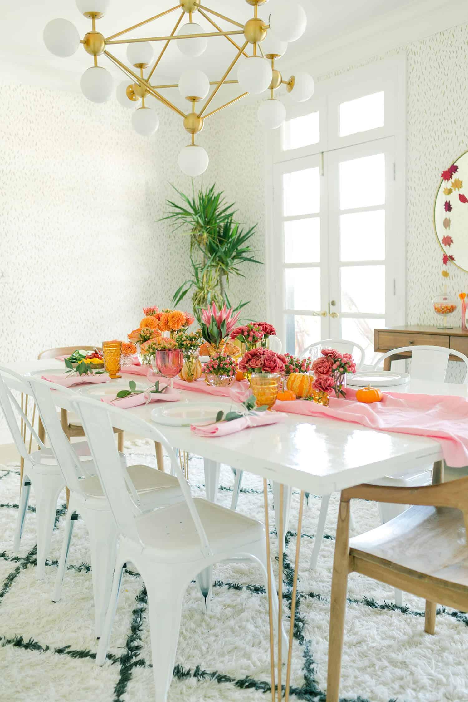 Mesa posta decorada com vasos e flores de cores, formas e tamanhos variados
