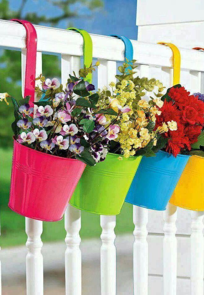 Flores artificiais em vasos coloridos decoram a varanda dessa casa