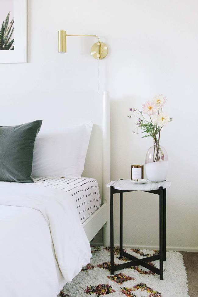 A decoração clean desse quarto apostou em um vaso com flores discretas e que seguem o mesmo tom sóbrio da decor