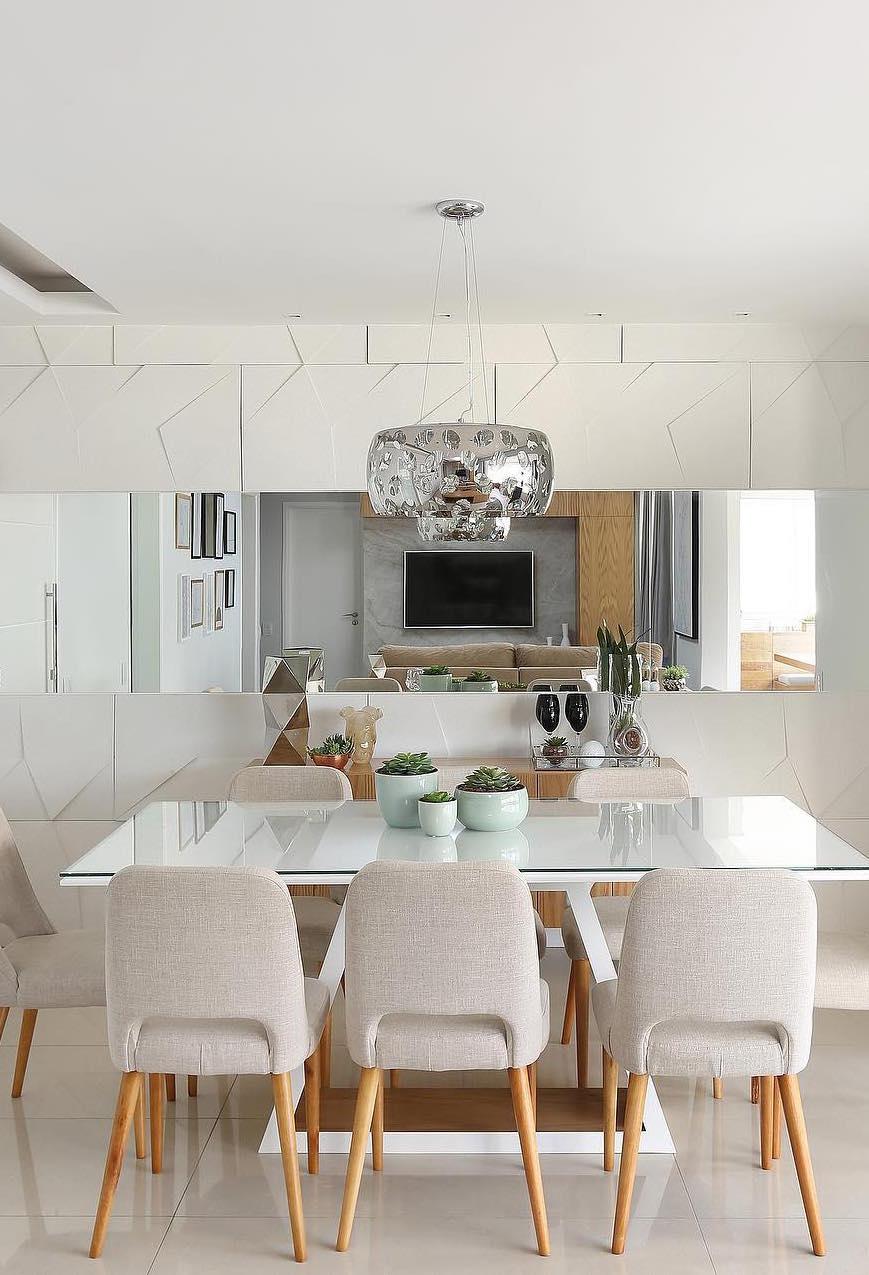 Tons claros, espelho e metais compõe essa sala de jantar de proposta clean e moderna