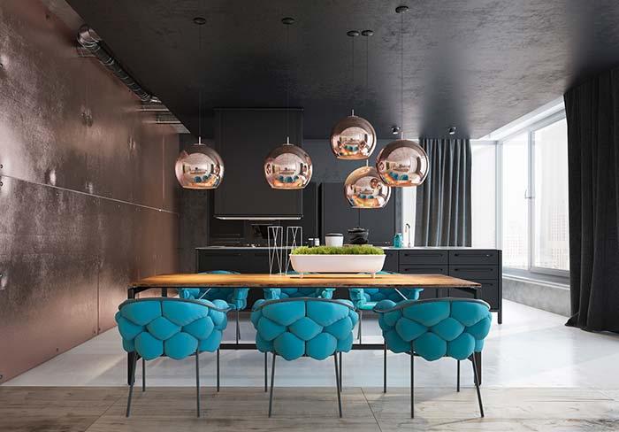 Cadeiras de estofamento azuis dessa sala de jantar quebram a predominância dos tons escuros