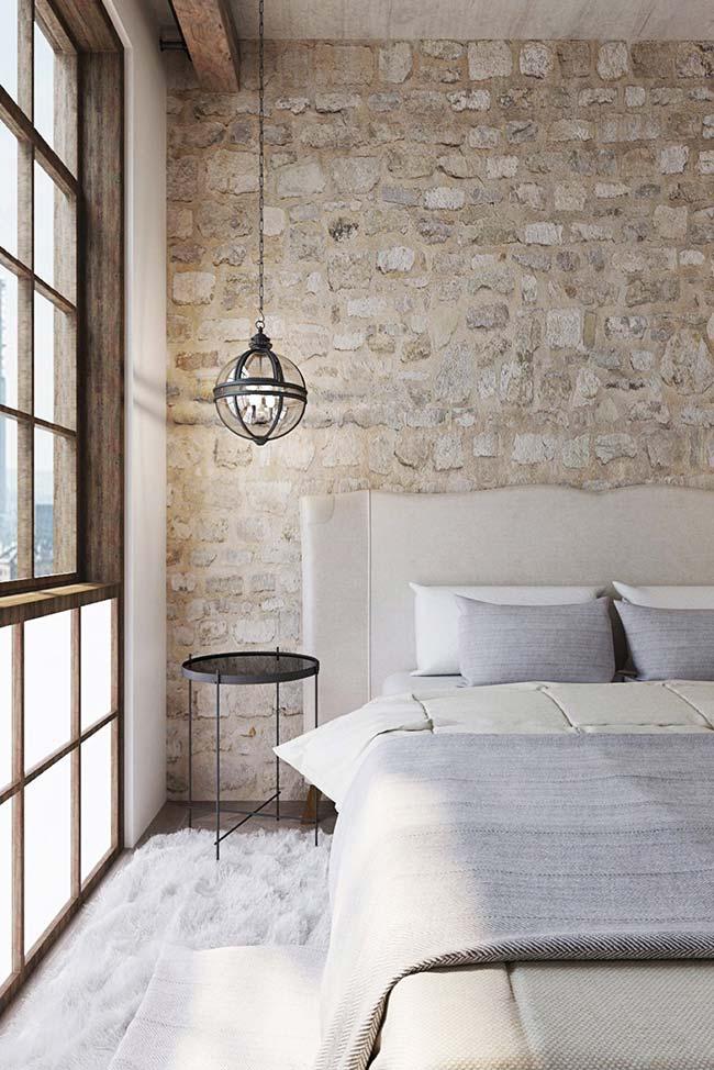 Parede de pedras decorativas se tornou o destaque desse quarto de casal