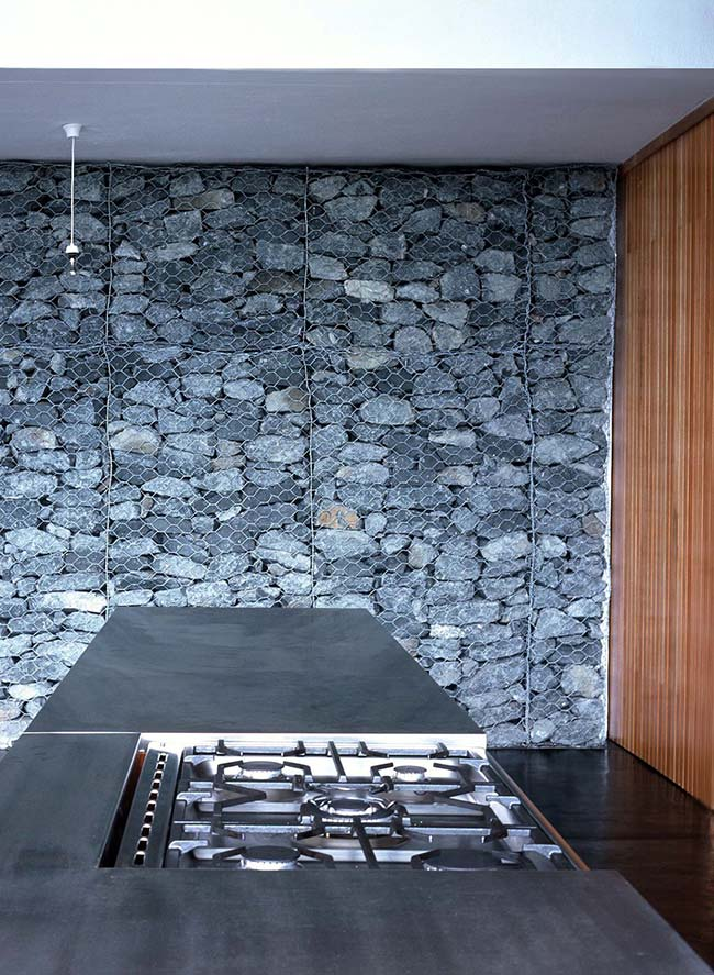 A estrutura usada nos muros de arrimo, os gabiões de pedra, foi utilizada nessa cozinha com muito sucesso, mantendo apenas a função decorativa