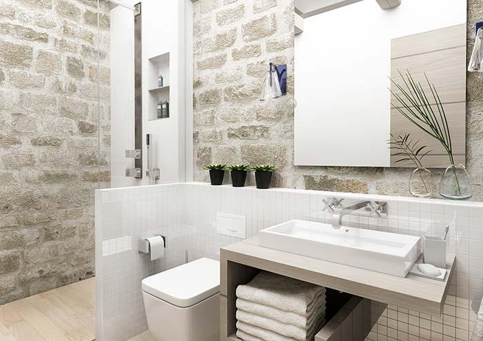 Banheiro de pedras rústicas combinadas a materiais nobres, como o vidro e a porcelana