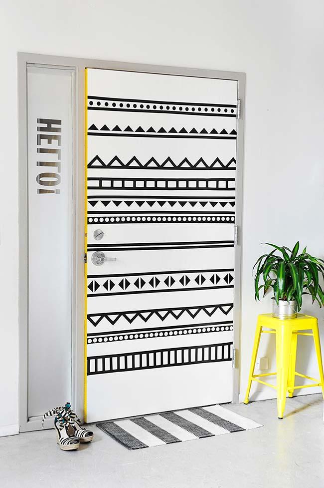 Porta decorada com fita isolante; o banco amarelo ao lado ajuda a realçar e valorizar o trabalho na porta