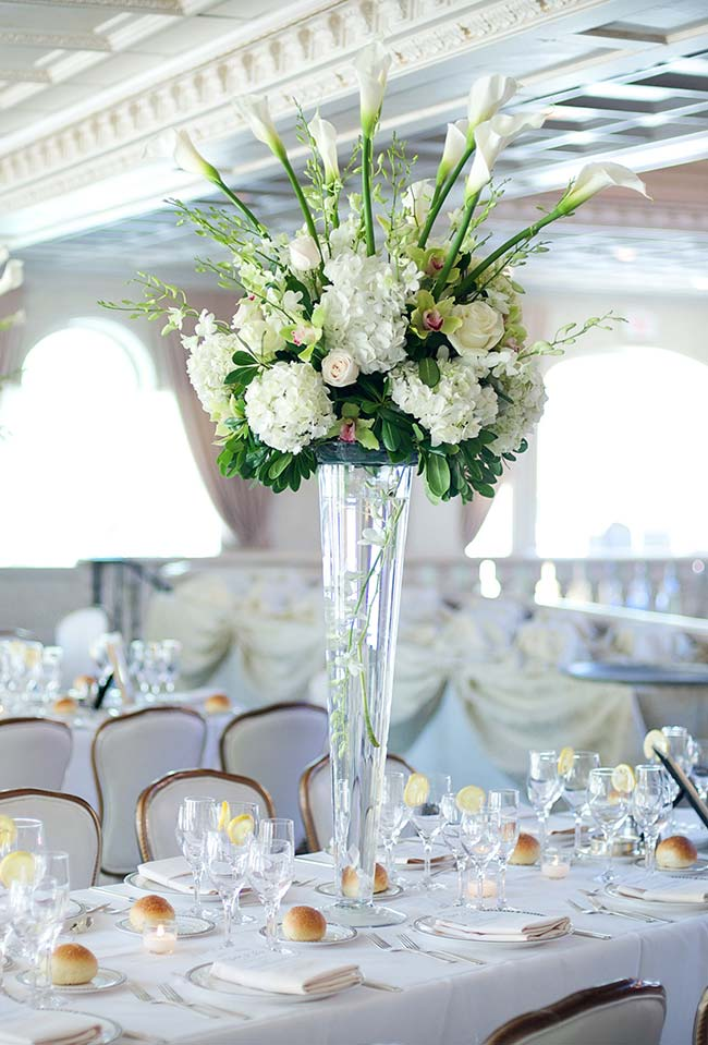 Arranjo algo e elegante de copos de leite e outras flores decorando o centro da mesa dos convidados